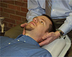 Chiropractor's hands on patient's neck