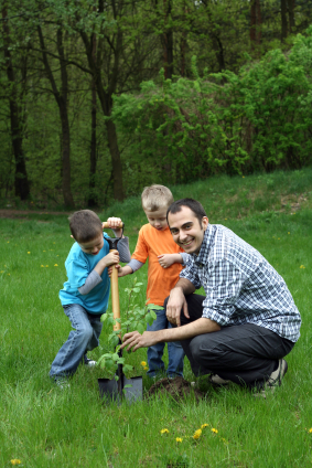 A man and two small children smile as they plant a tree in a green yard.