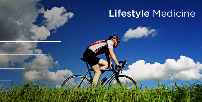 Lifestyle Medicine person on bicycle riding through green grass