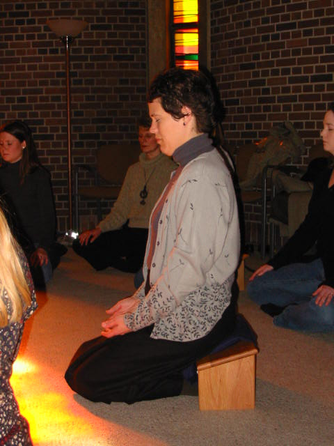 Woman kneeling on a meditation bench. Her hands are in her lap and her eyes are closed.