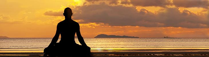 Human being meditating on beach at sunset