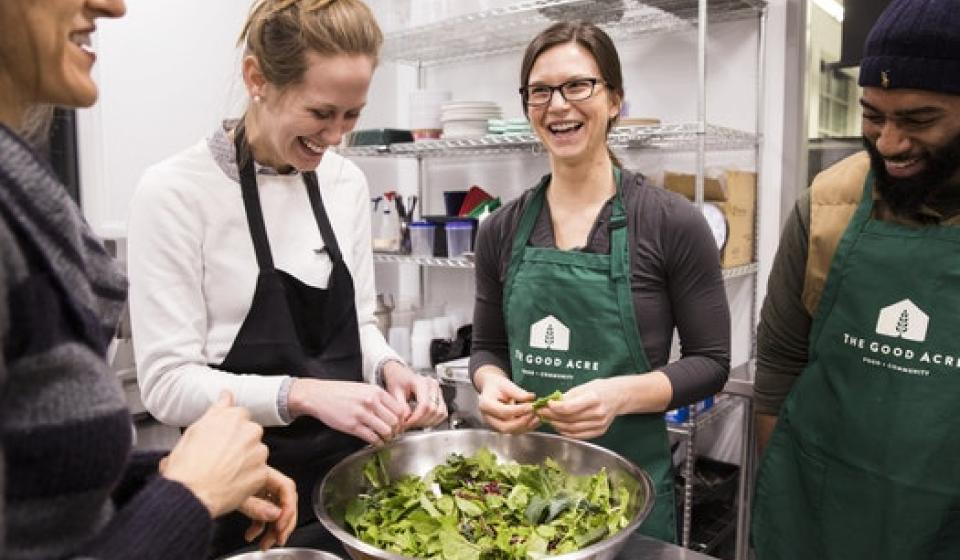 Photo from StarTribune.com of students and faculty cooking in kitchen