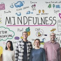 Group of people with illustrated thought bubbles describing mindfulness, including spending time in nature, positive thinking, happiness, walking a dog, bathing, meditating