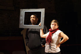 A woman and man on a dark stage. The woman is holding up a cardboard television frame, and the man is standing with his head in the frame and speaking.